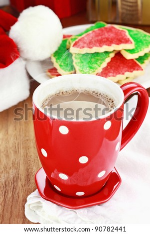 Cup of hot cocoa with Christmas cookies and Santas hat in the background. Shallow depth of field. - stock photo
