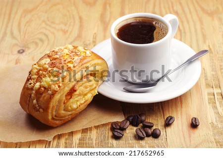 Cup of hot coffee and bun with cheese on old wooden table - stock photo