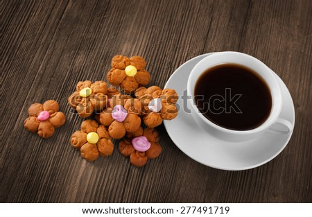 Cup of hot coffee and cookies on the wooden table - stock photo