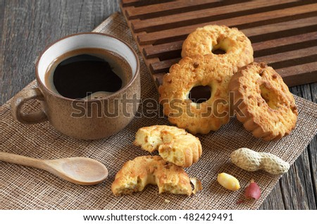 Cup of hot coffee and cookies rings with nuts on old wooden table
