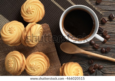 Cup of hot coffee and cookies with caramelized milk filling for breakfast on rustic wooden background, top view