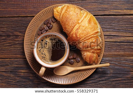 Cup of hot coffee and croissant in plate on dark wooden table, top view