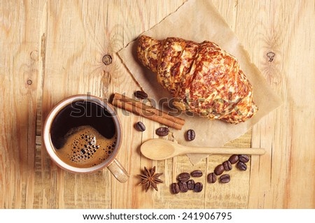 Cup of hot coffee and croissant with cheese for breakfast on a rustic wooden table, top view - stock photo