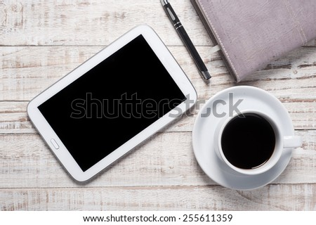 Cup of hot coffee and diary on wood table background - stock photo
