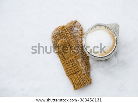 cup of hot coffee and gloves in the snow - stock photo