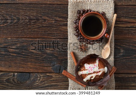Cup of hot coffee and muffin in brown paper on dark wooden background, top view