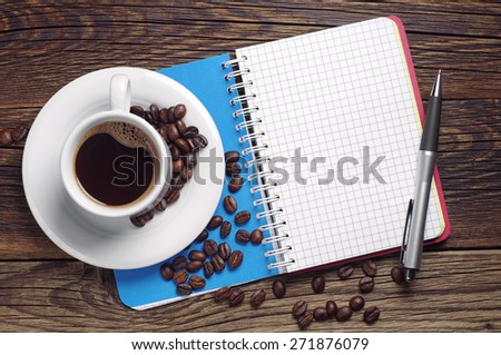 Cup of hot coffee and opened notebook with empty page on table, top view - stock photo