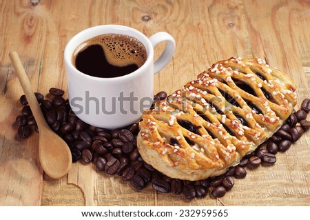 Cup of hot coffee and sweet bun with jam on old wooden table