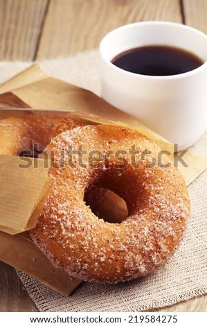 Cup of hot coffee and sweet donut on wooden background - stock photo