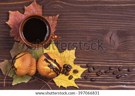 Cup of hot coffee and two sweet cupcakes on wooden table, top view - stock photo
