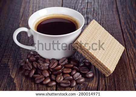 Cup of hot coffee and wafers with caramelized condensed milk on dark wooden background - stock photo