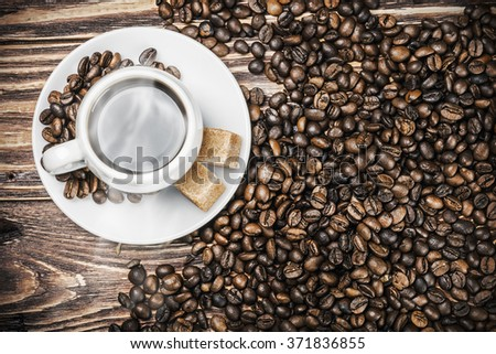cup of hot coffee in coffee beans roasted. Focus on the coffee beans on the table - stock photo