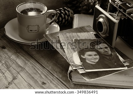 cup of hot coffee next to old photo camera, antique photos and old book on wooden table. black and white style image. selective focus - stock photo