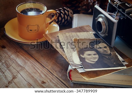 cup of hot coffee next to old photo camera, antique photos and old book on wooden table. vintage filtered image. selective focus - stock photo