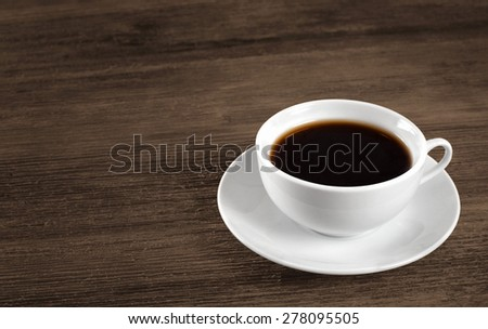 Cup of hot coffee on a wooden table.