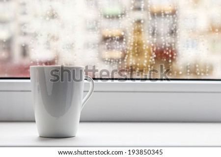 cup of hot coffee on the window sill wet from the rain - stock photo