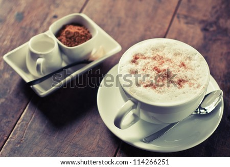 cup of hot coffee on wood table, vintage style - stock photo