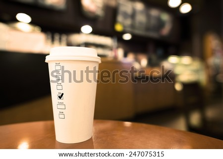 Cup of Hot Coffee on Wood Table. With Label on the Cup Tick on Milk - stock photo