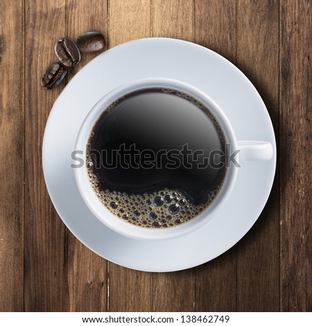 Cup of hot coffee on wood table with smoke coming out and coffee beans