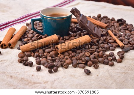 Cup of hot coffee with cinnamon sticks, bitten bar of chocolate on vintage texture background, selective focus - stock photo