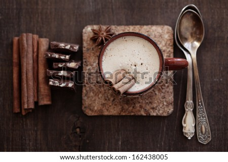 Cup of hot coffee with cinnamon sticks on vintage wooden background, selective focus - stock photo