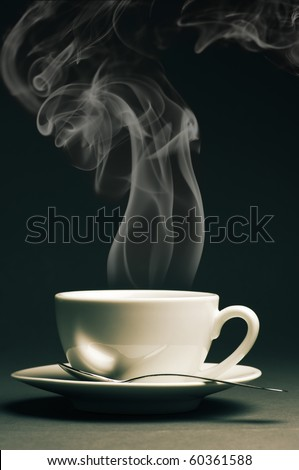 Cup of hot coffee with steam on dark background. Toned image. - stock photo