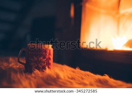 Cup of hot drink in front of warm fireplace. Holiday Christmas concept. Mug in red knitted mitten standing near fireside. Cozy relaxed magical atmosphere in a chalet. - stock photo