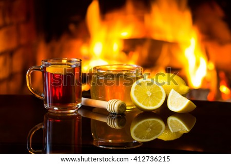 Cup of hot drink wine, bowl of honey and lemon in front of warm fireplace. Magical relaxed cozy atmosphere near fire. - stock photo