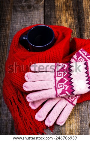 Cup of hot drink wrapped by red scarf and gloves on wooden board.Closeup - stock photo