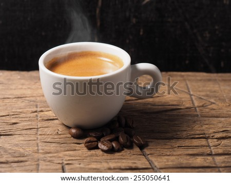 Cup of hot espresso coffee and coffee crop on wood board - stock photo