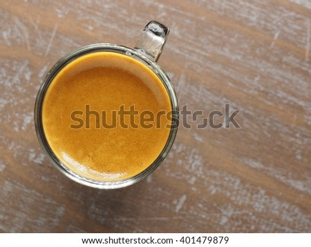 Cup of hot espresso coffee on wood table, background