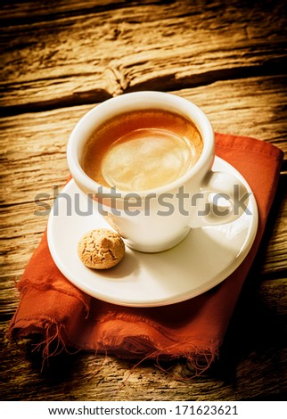 Cup of hot frothy espresso coffee served on a rustic cloth with a small macaroon in a rural country cafeteria on a weathered wood surface with vignetting and copyspace - stock photo