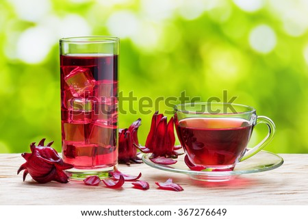 Cup of hot hibiscus tea (karkade, red sorrel, Agua de flor de Jamaica) and the same cold drink with ice cubes in glass on nature background. Magenta-color calyces (sepals) of roselle flowers on table. - stock photo