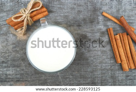 cup of hot milk with cinnamon, closeup , wooden background - stock photo