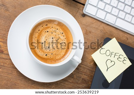 Cup of hot tasty delicious coffee with computer keyboard on a rustic table and stay coffee note - stock photo