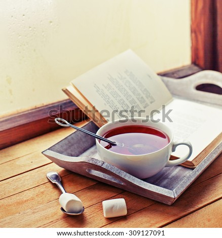 Cup of hot tea and book on a wooden tray - stock photo