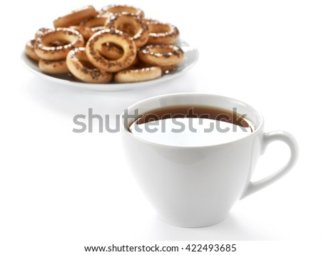 Cup of hot tea and cookies on white background