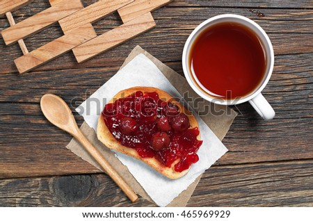 Cup of hot tea and roasted white bread with cherry jam for breakfast on table, top view