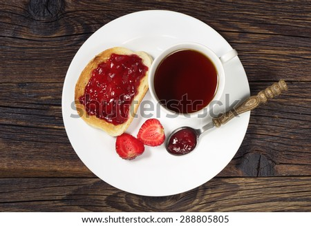 Cup of hot tea and toasted bread with jam in plate on old wooden table, top view - stock photo