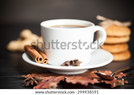 Cup of hot tea on wood background with leaf. Autumn.