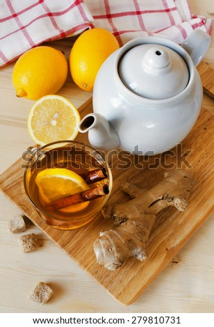Cup of hot tea with a lemon and ginger on a table - stock photo