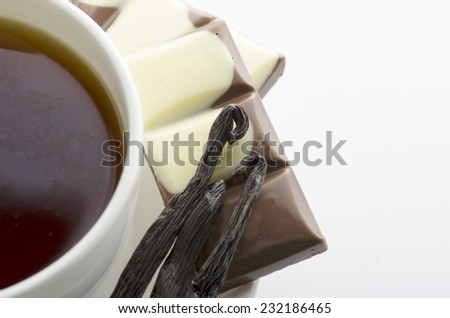 Cup of hot tea with dark chocolate - stock photo