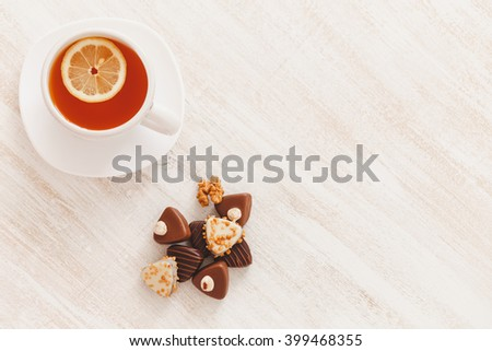 Cup of hot tea with lemon and chocolate candy on white wooden table, selective focus - stock photo