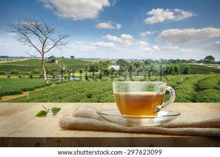 Cup of hot tea with sacking on the wooden table and the tea plantations background - stock photo