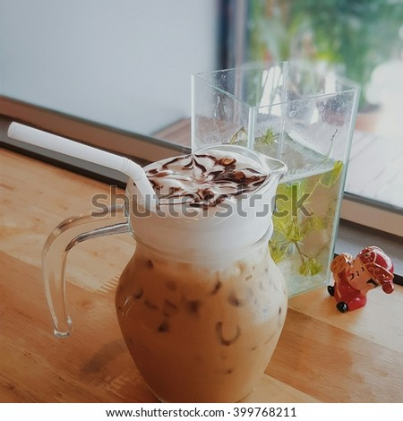 cup of Ice Caramel Macchiato and ice cappuccino on the wooden table in coffee shop blurry background. - stock photo
