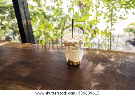 cup of Ice Coffee on  wooden table in coffee shop blurry background - stock photo