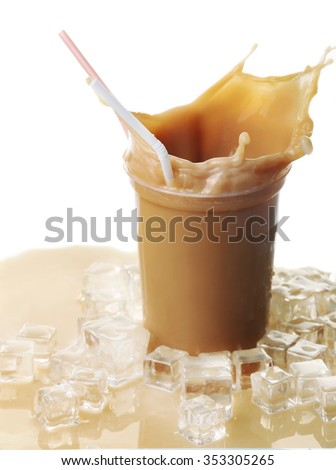 Cup of ice coffee with splashes on table - stock photo