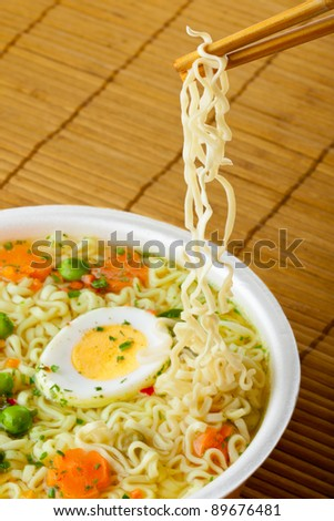 Cup of instant noodles with vegetables on a traditional mat - stock photo