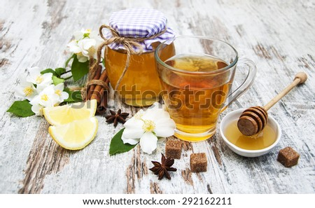 Cup of jasmin tea with honey on a wooden background - stock photo