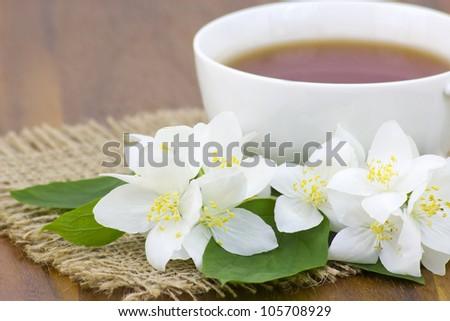 Cup of jasmine tea and jasmine flowers - stock photo